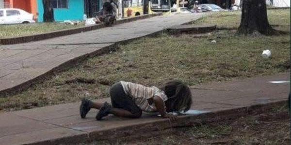 criança indígena bebendo água da poça